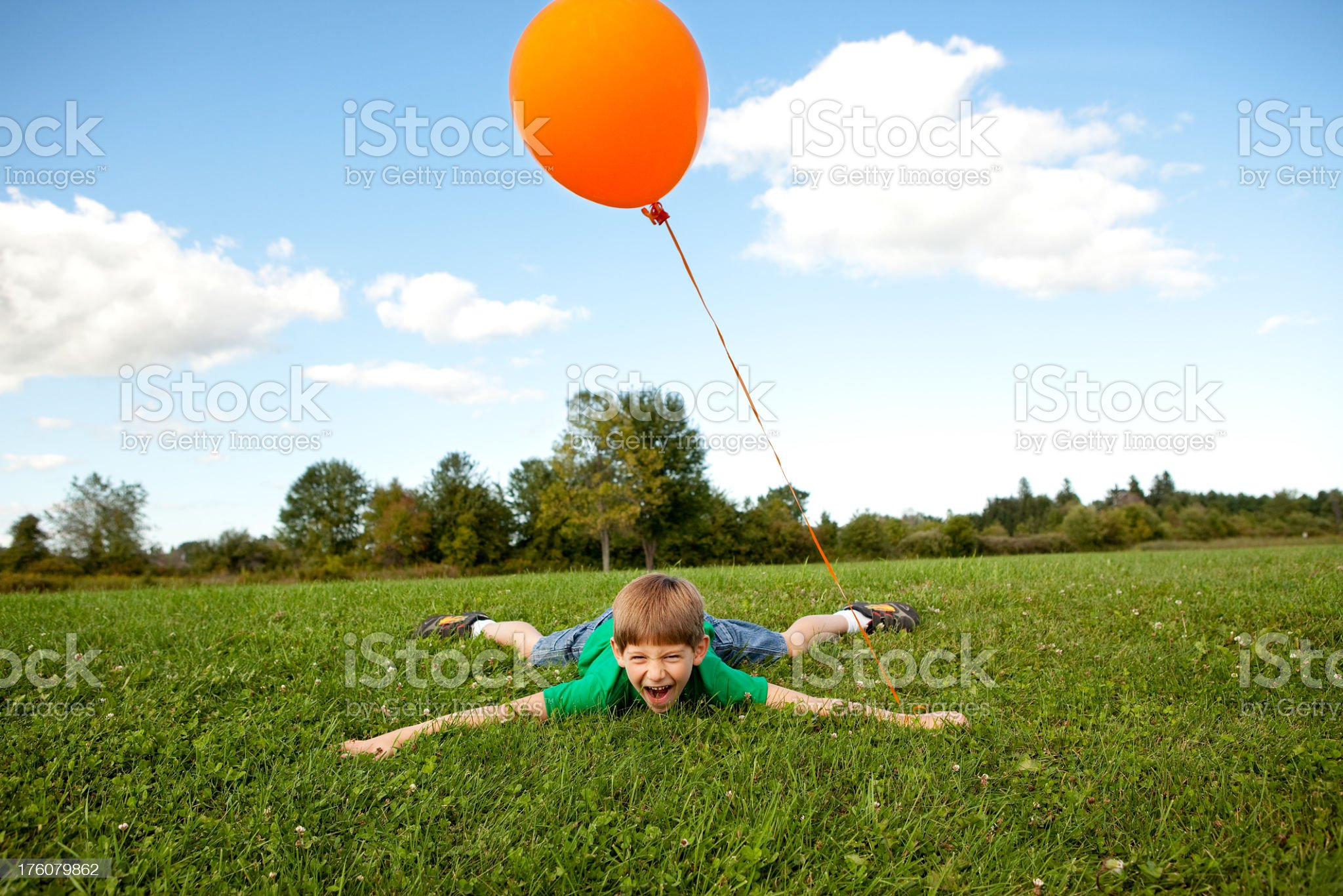Happy Boy with Balloon Lying in the Grass royalty-free stock photo