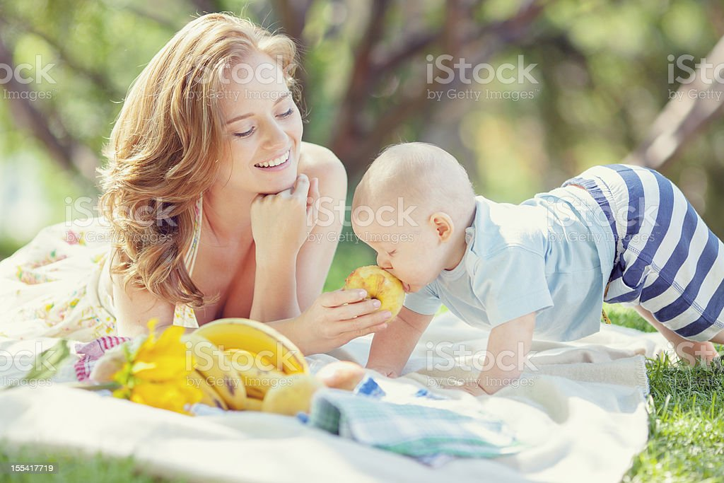 happy boy with mom eating in park royalty-free stock photo