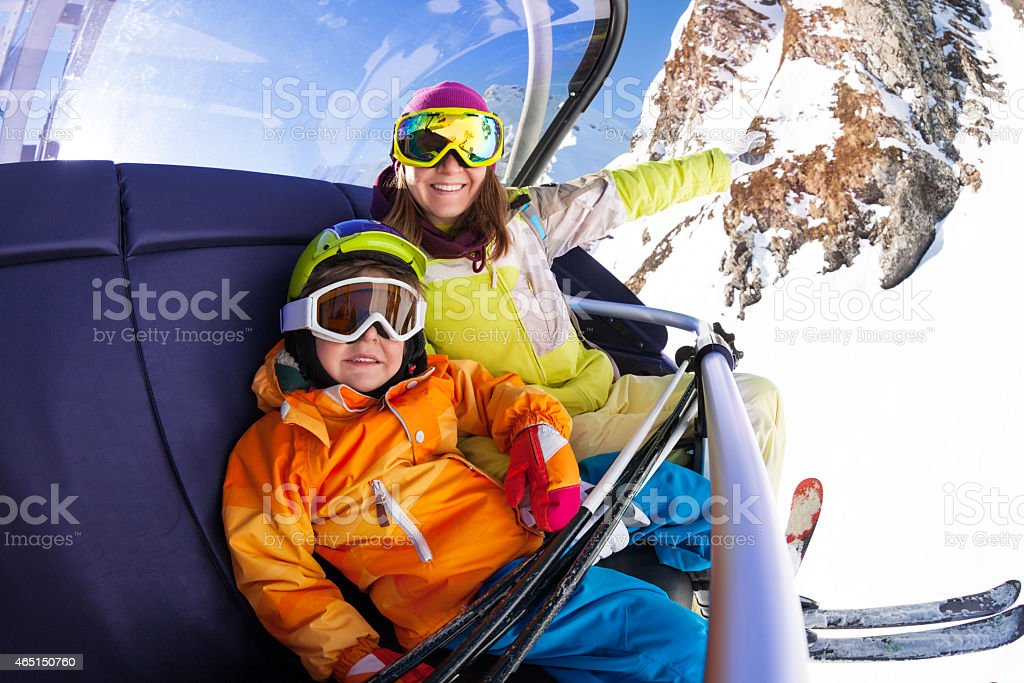 Happy boy with mother on ski chair lift stock photo