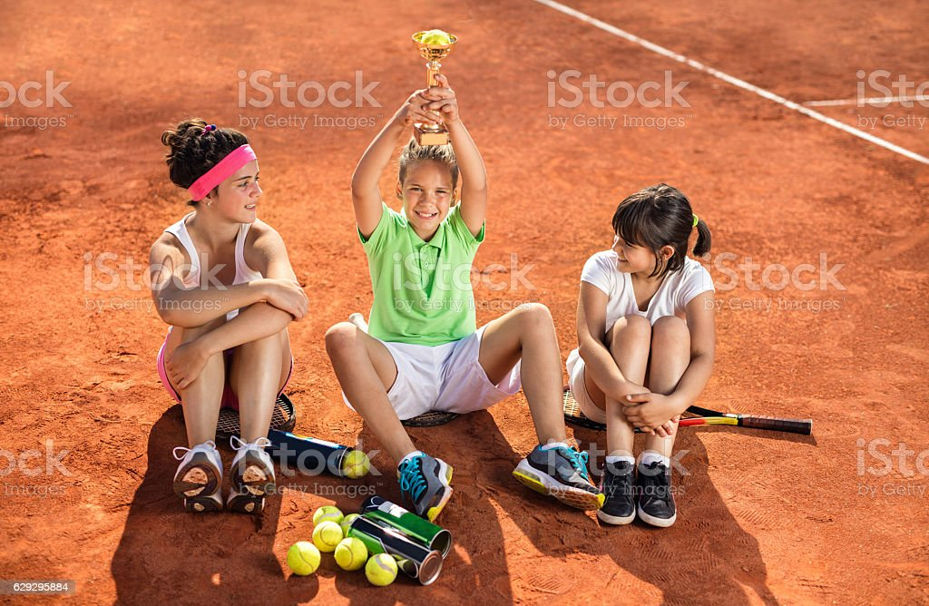 Happy boy with winning trophy celebrating on tennis court. stock photo