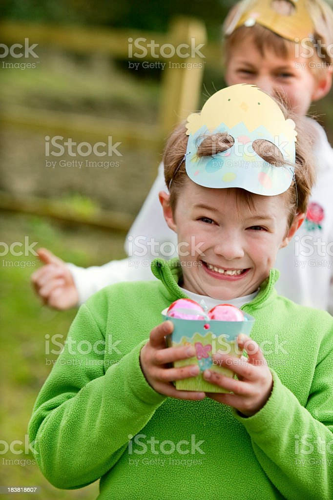 happy boys holding eggs on easter hunt outdoors stock photo