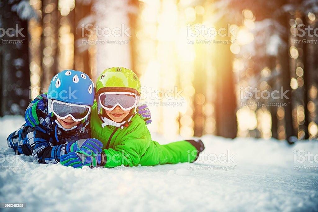 Happy boys in ski outfits enjoying winter stock photo