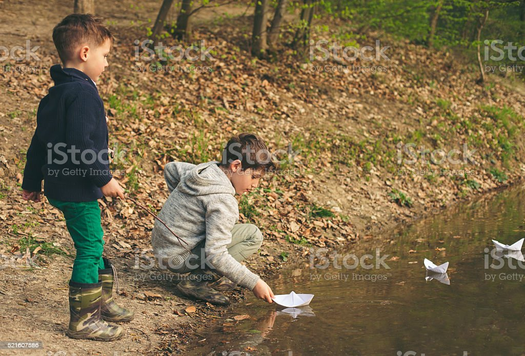Happy boys playing in river. stock photo