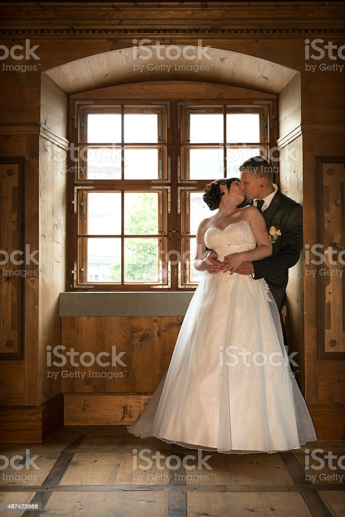 happy bridal couple standing at a window stock photo