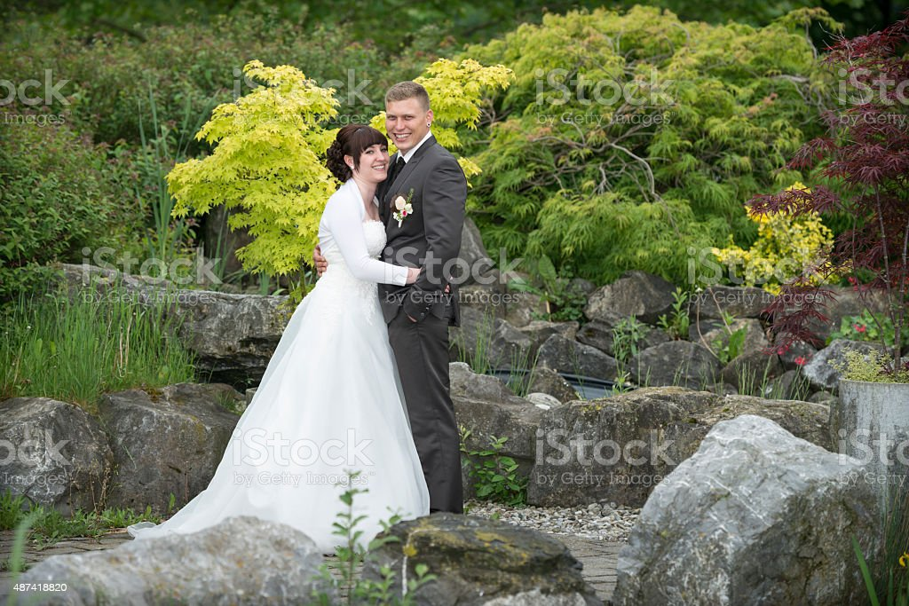 happy bridal couple standing outdoors in a park stock photo