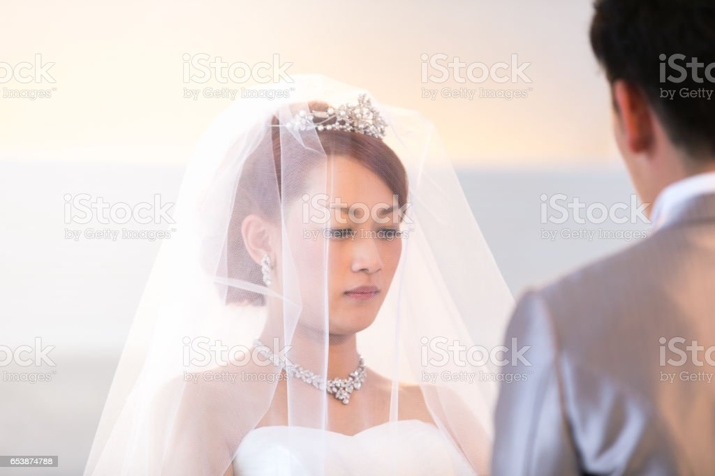 Happy bride and groom exchaning wedding ring in chapel stock photo