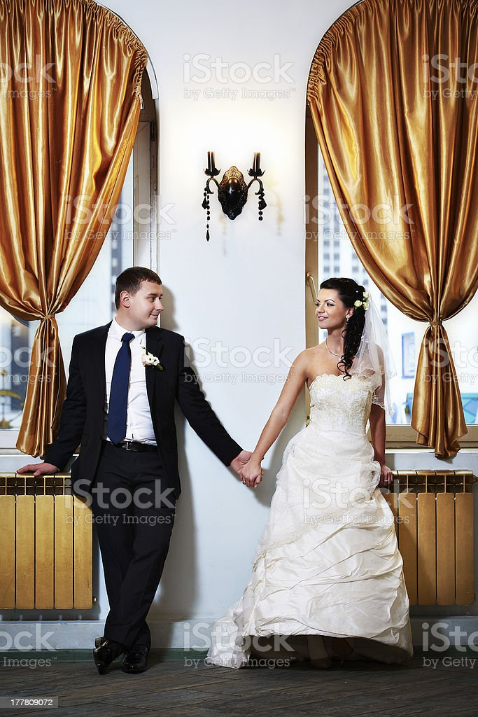 Happy bride and groom hold each other's hand in interior stock photo