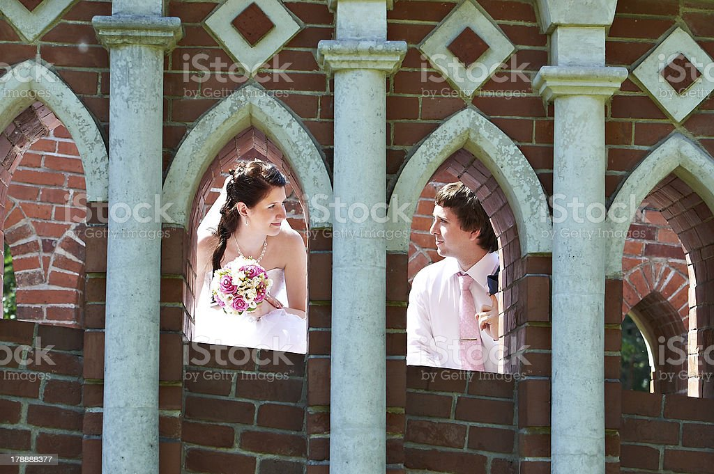 Happy bride and groom in windows of brick wall royalty-free stock photo