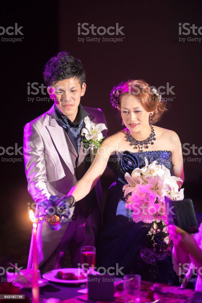 Happy bride and groom presenting candlelight service at wedding party stock photo