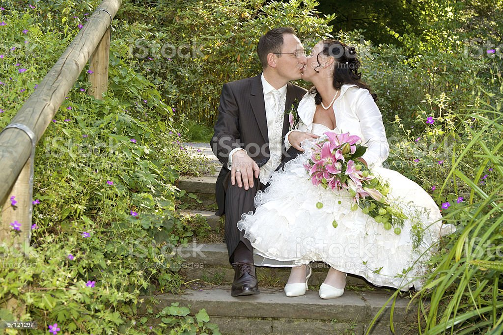Happy Bride and Groom sitting kissing on a stairway royalty-free stock photo