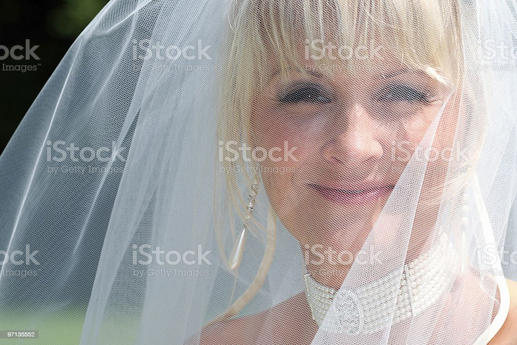 Happy bride looks through her veil royalty-free stock photo