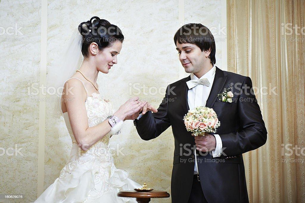 Happy bride wears wedding ring her groom royalty-free stock photo