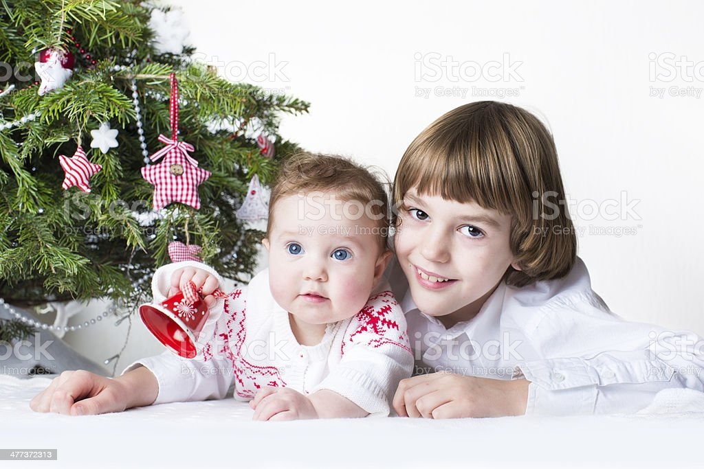 Happy brother and baby sister playing together under Christmas tree royalty-free stock photo