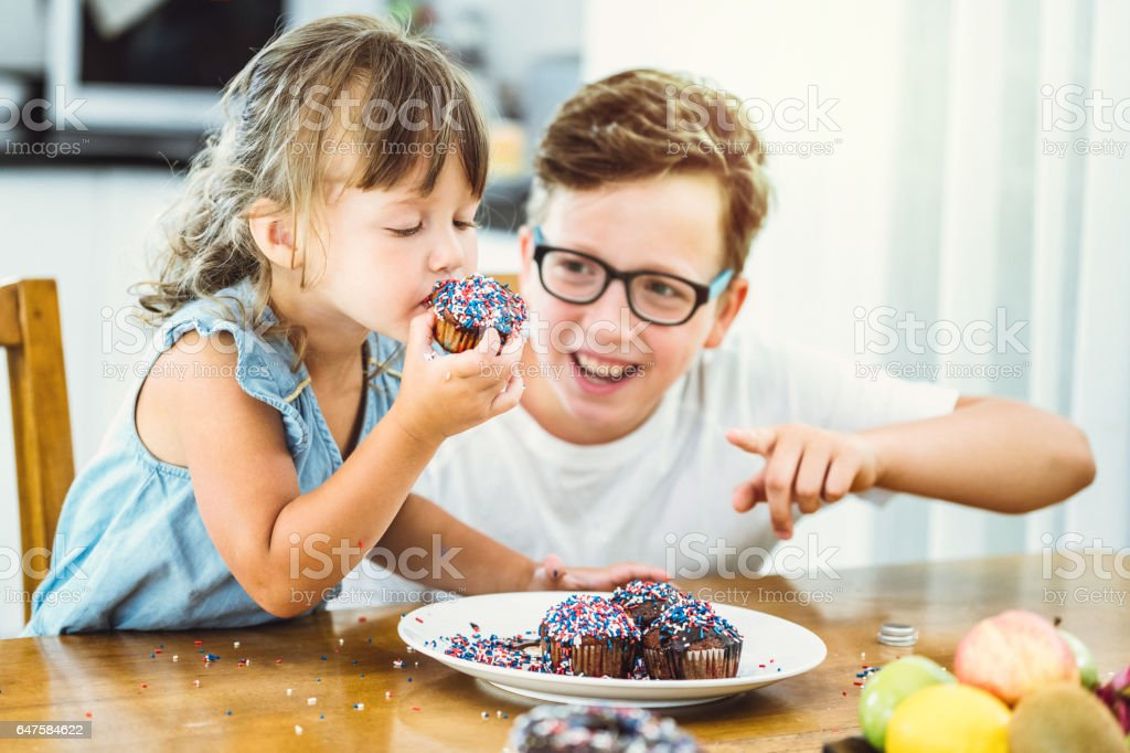 Happy brother and sister eating delicious donuts stock photo