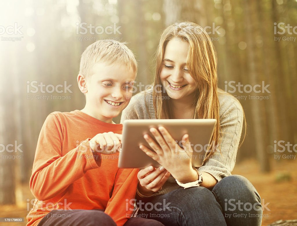 Happy brother and sister examine new digital tablet in forest stock photo