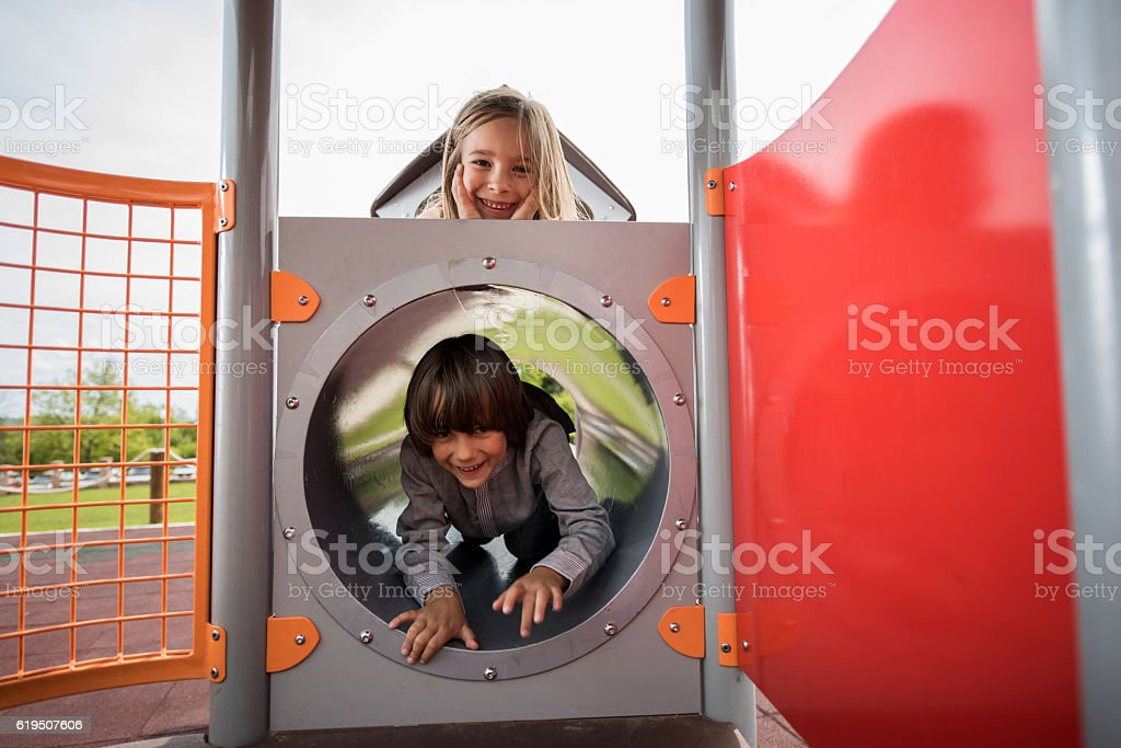 Happy brother and sister playing together at the playground. stock photo