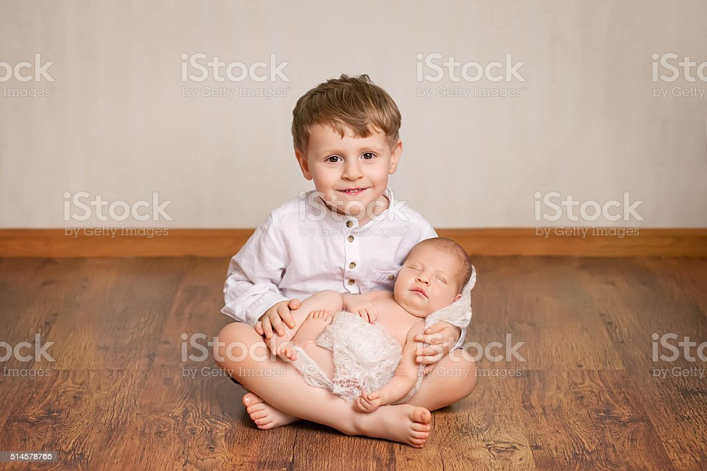 Happy brother holding his newborn baby sister stock photo