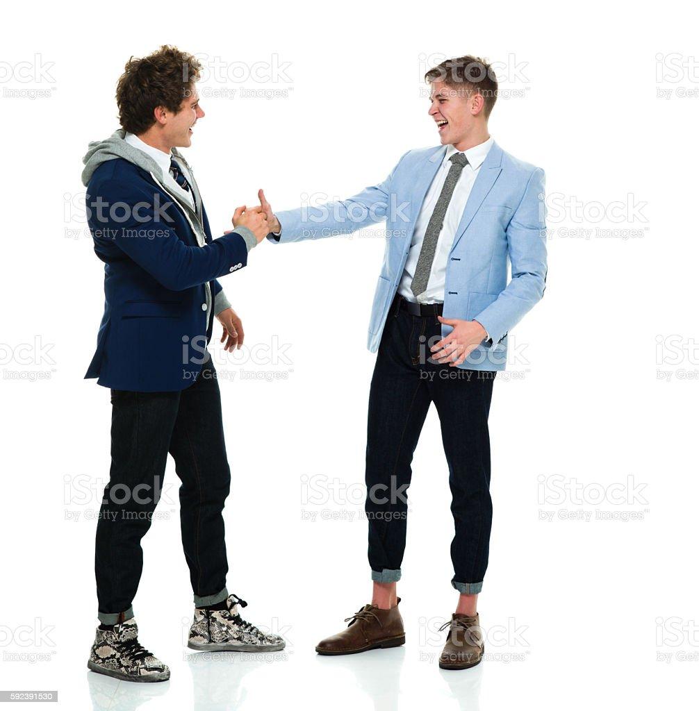 Happy brothers giving handshake stock photo