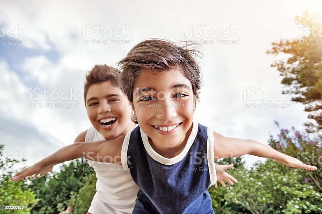Happy brothers playing outdoors stock photo