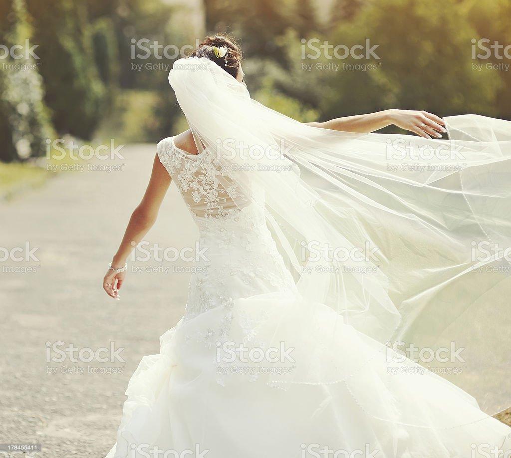 happy brunette bride spinning around with veil stock photo