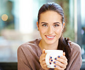 Happy brunette with mug in hands looking to camera