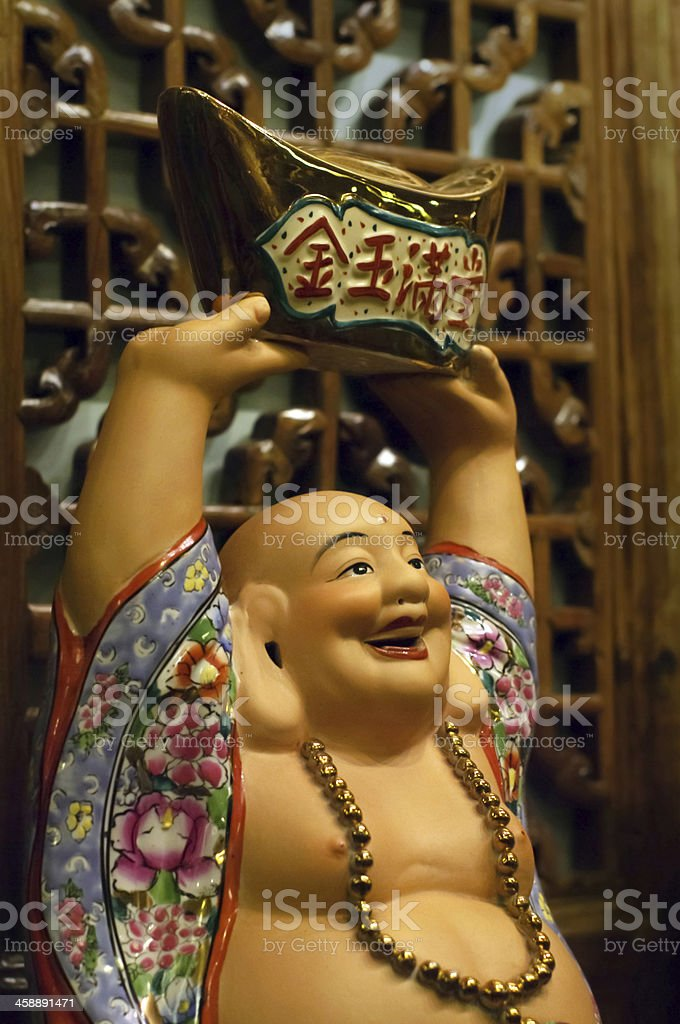 Happy Buddha Carrying Gold Money Porcelain Figure stock photo