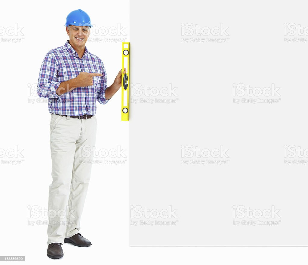 Happy builder pointing at spirit level on wall royalty-free stock photo