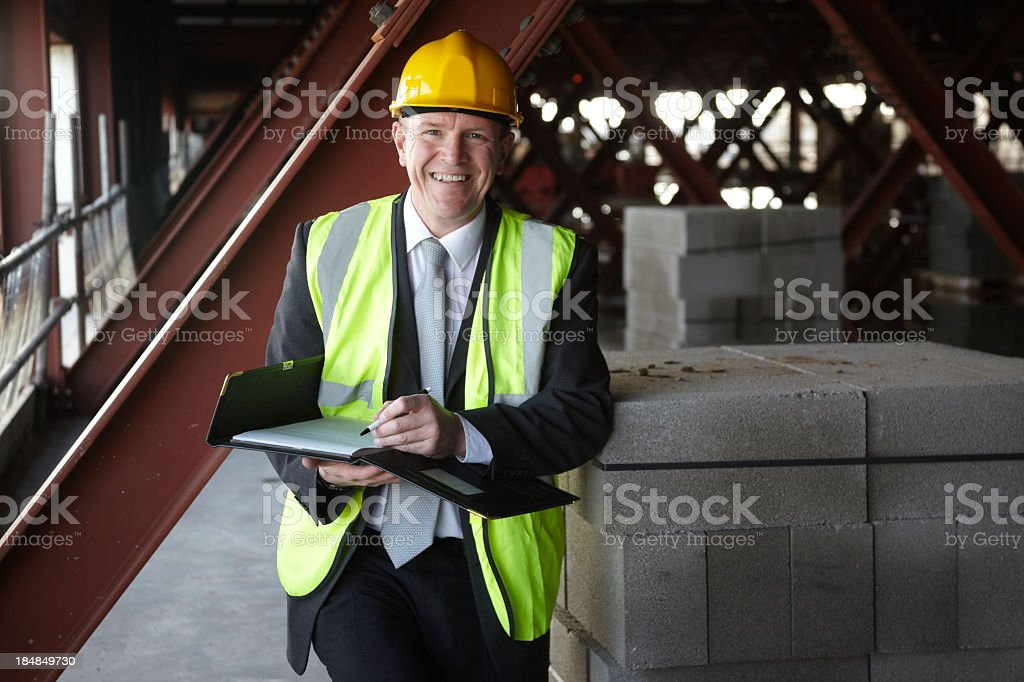 Happy building executive on construction site stock photo