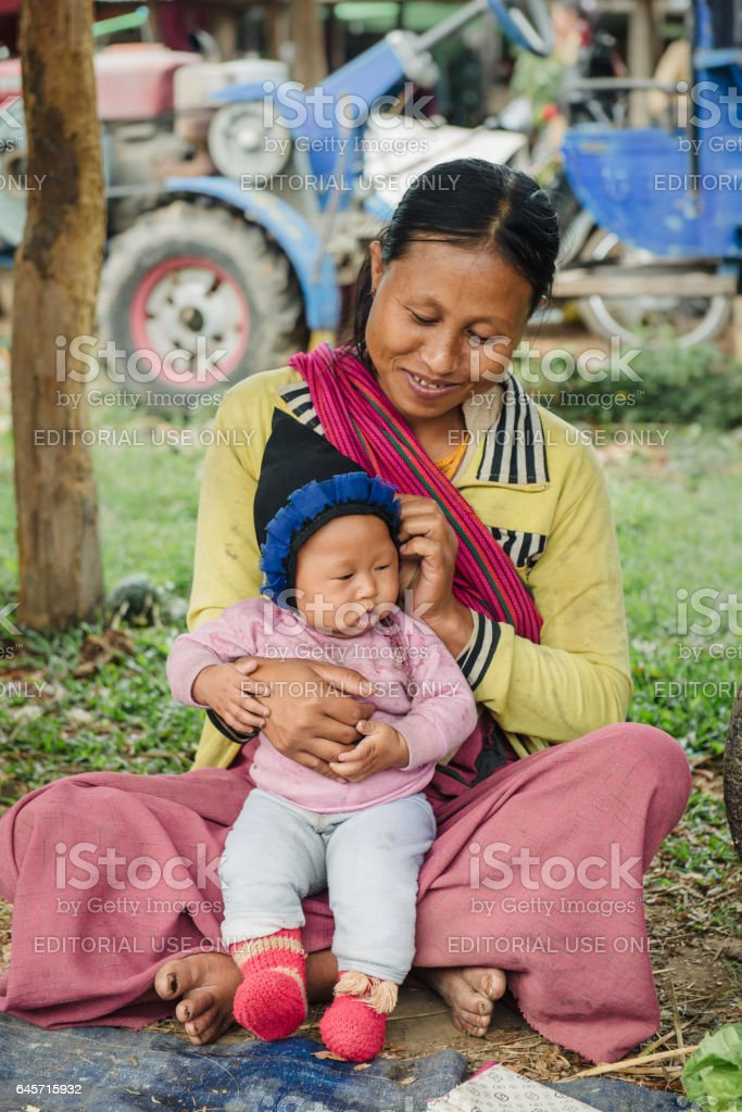 Happy Burmese woman with baby selling goods stock photo