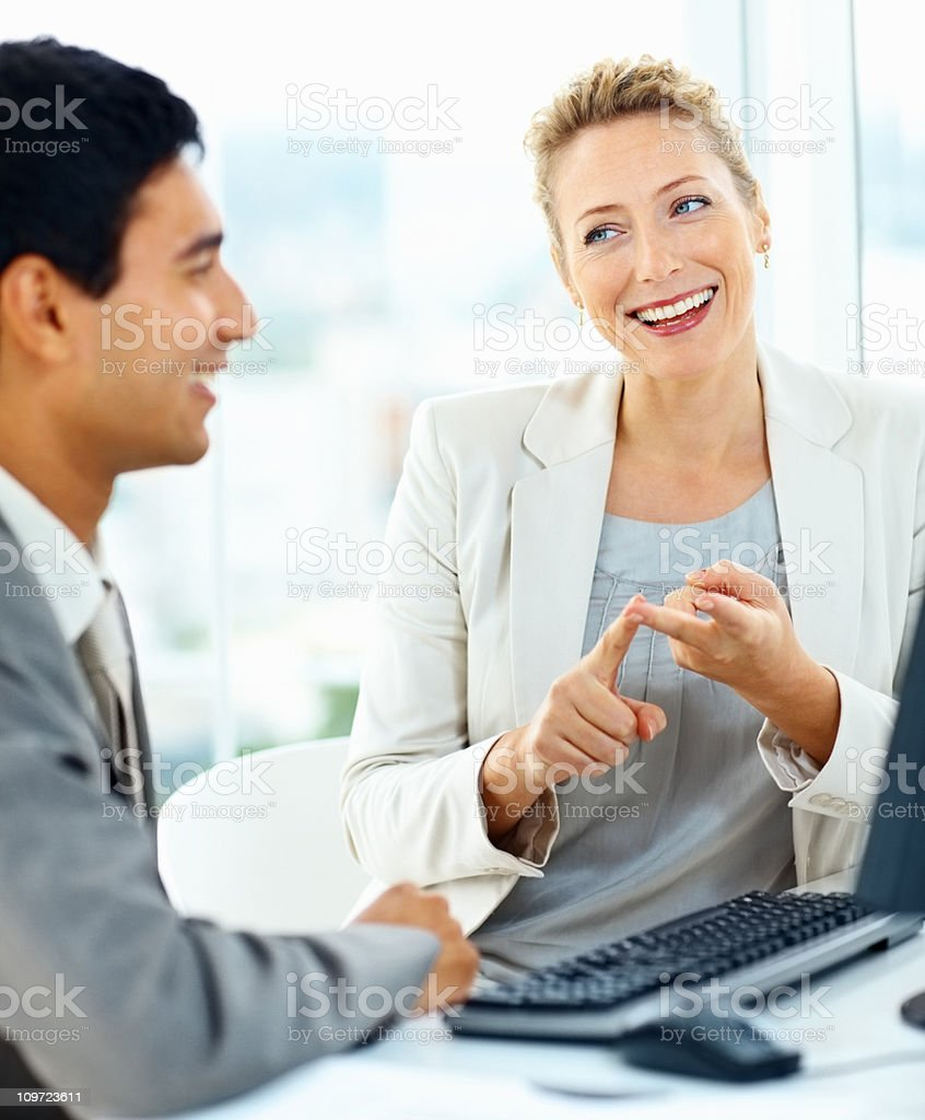 Happy business colleagues discussing while working on computer royalty-free stock photo
