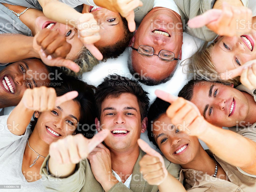 Happy business colleagues showing thumbs up sign royalty-free stock photo