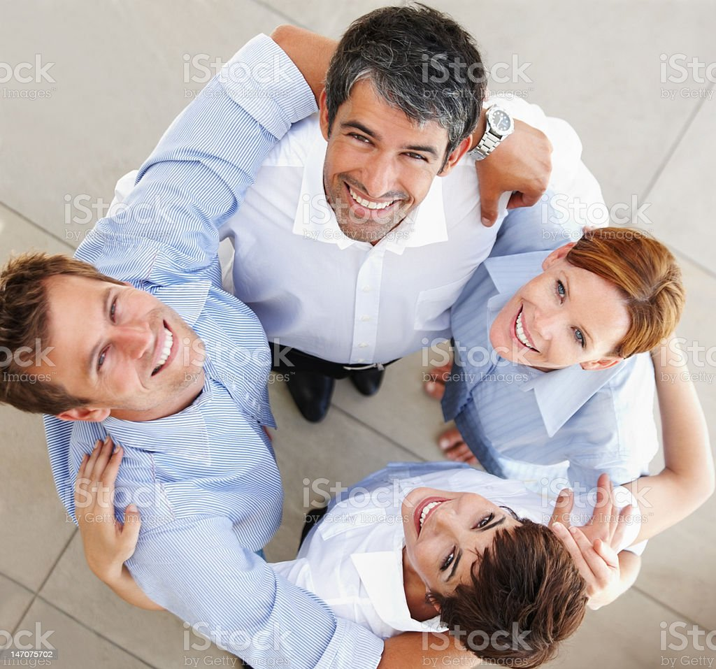 Happy business colleagues standing together in a huddle royalty-free stock photo