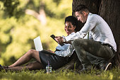 Happy business colleagues using wireless technology in the park.