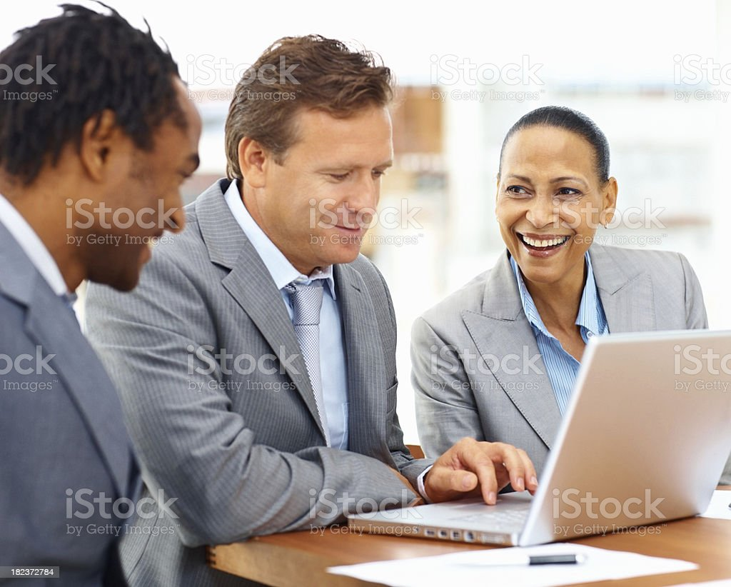 Happy business colleagues working together on a laptop royalty-free stock photo