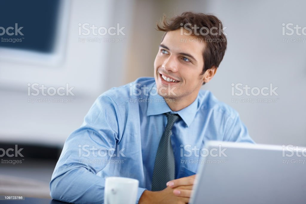 Happy business man looking away while in front of laptop royalty-free stock photo