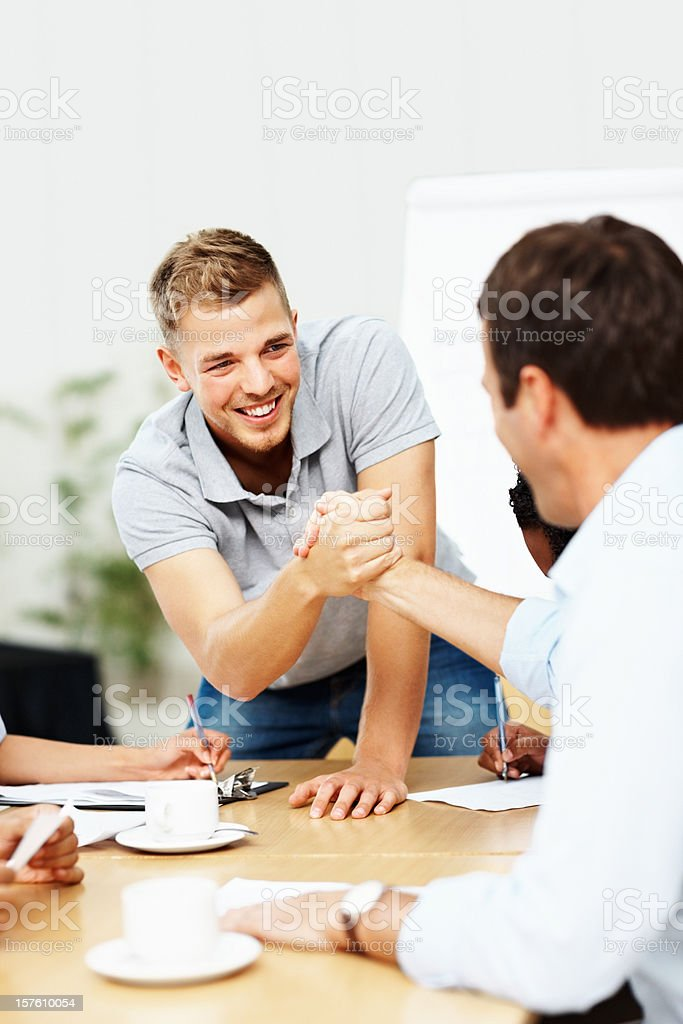 Happy business man shaking hands with colleague at a meeting royalty-free stock photo