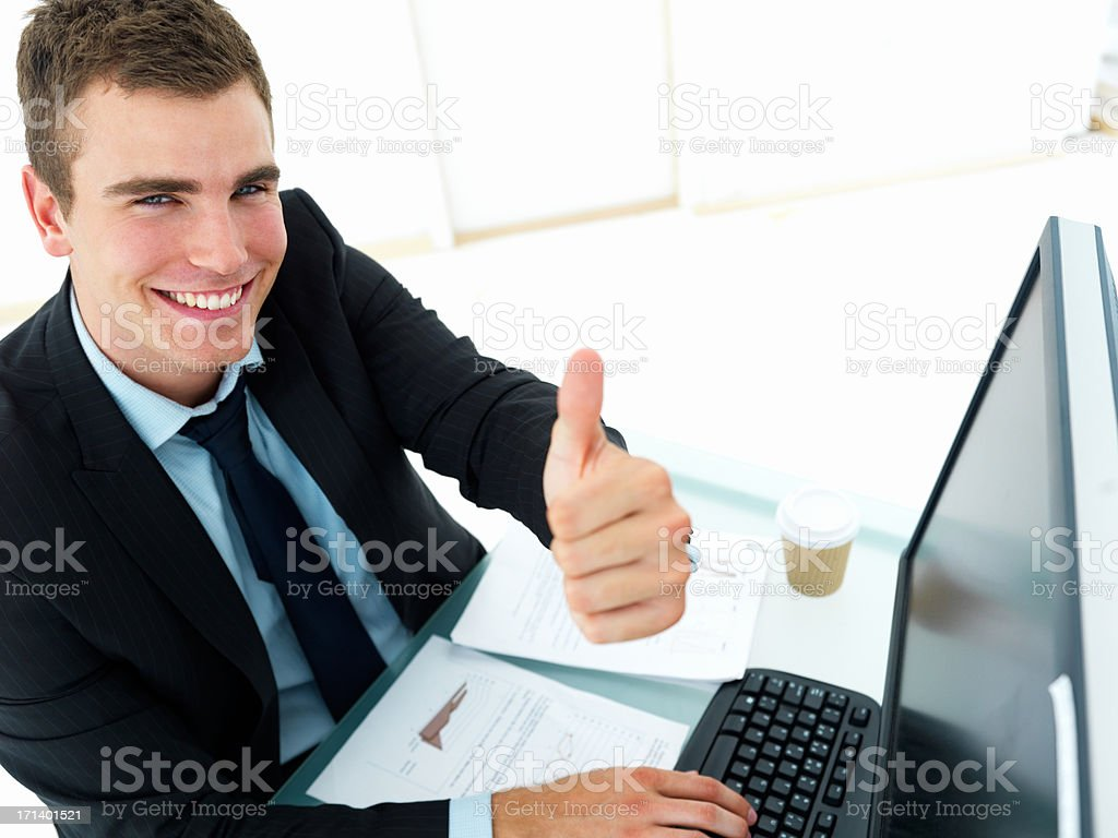 Happy business man sitting at office desk and showing thumbs up sign royalty-free stock photo