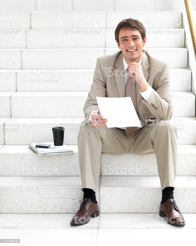 Happy business man sitting on stairs doing paperwork royalty-free stock photo