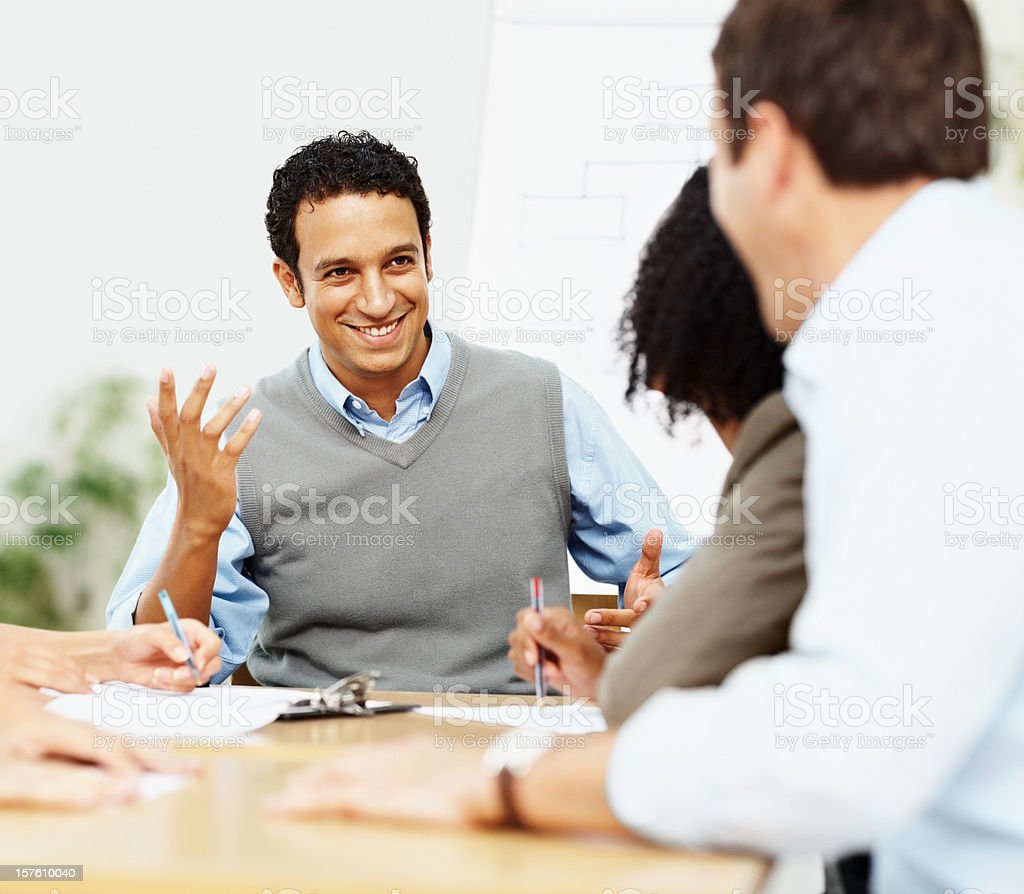 Happy business man sitting with a team in discussion royalty-free stock photo