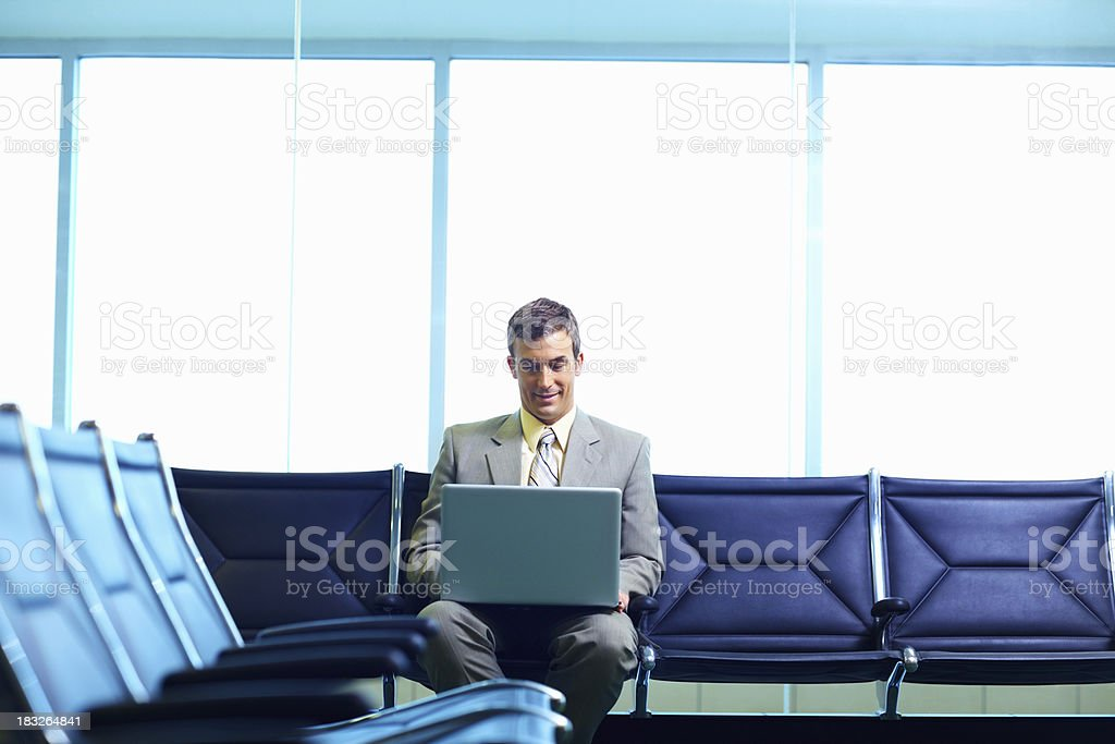 Happy business man working on laptop in an airport lounge stock photo