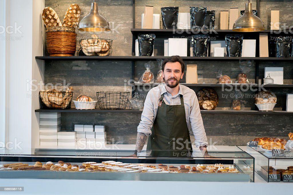 Happy business owner at a bakery stock photo