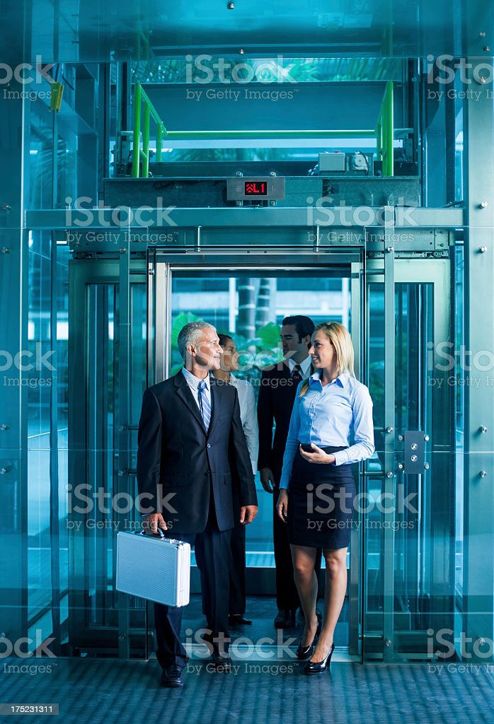 Happy business people coming out of the elevator stock photo