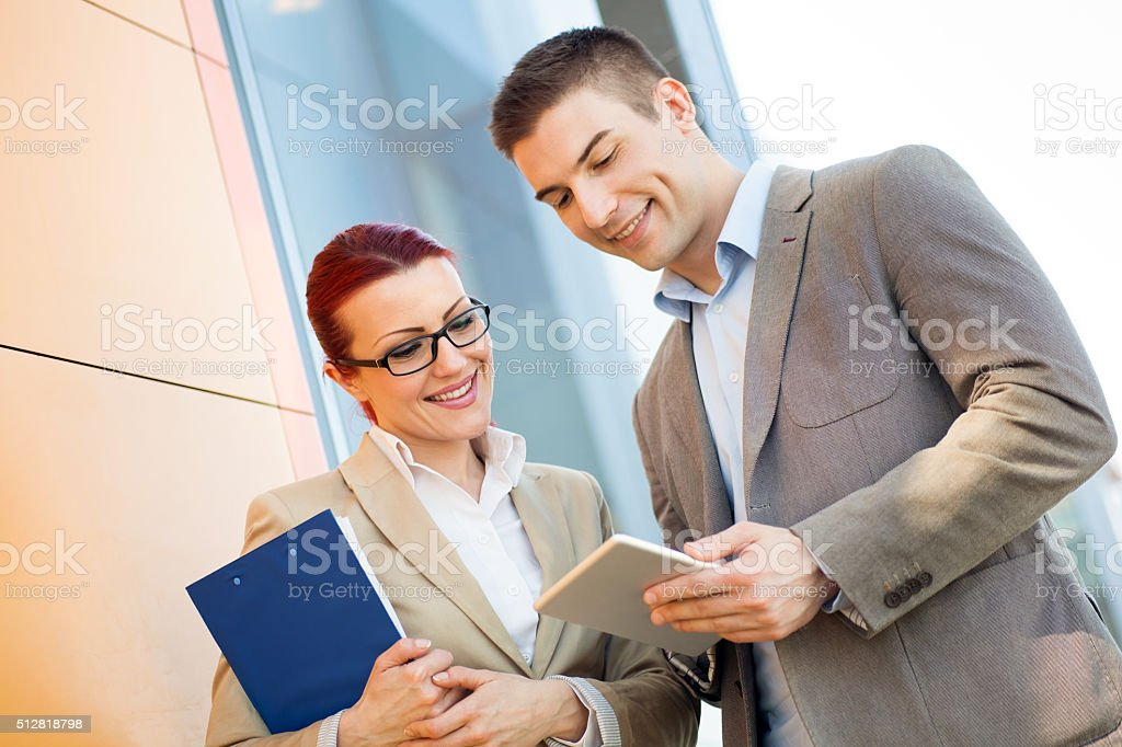 Happy business people cooperating while working on digital table stock photo