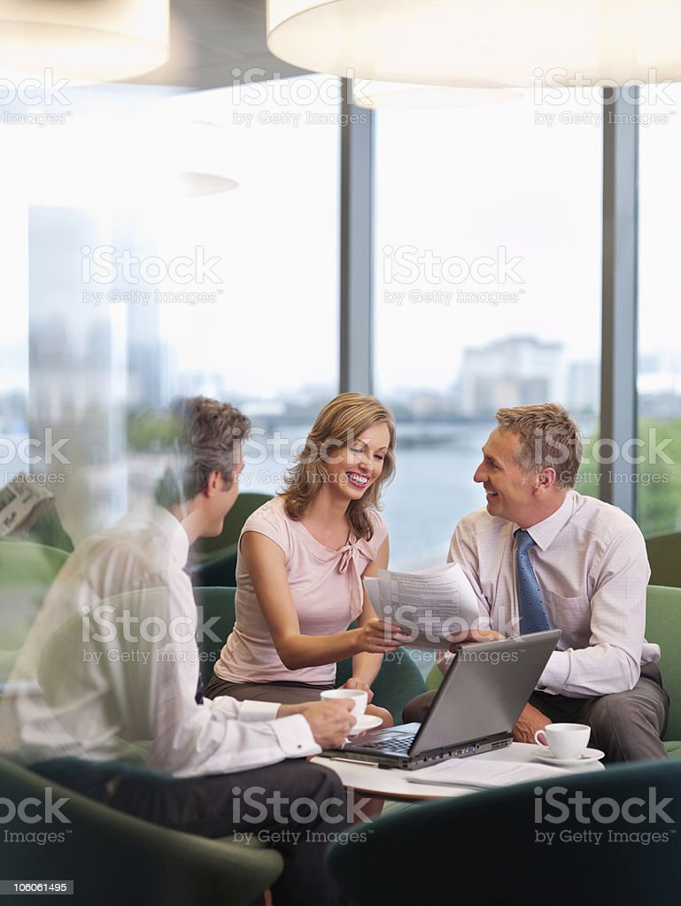 Happy business people doing paperwork with laptop at office canteen royalty-free stock photo