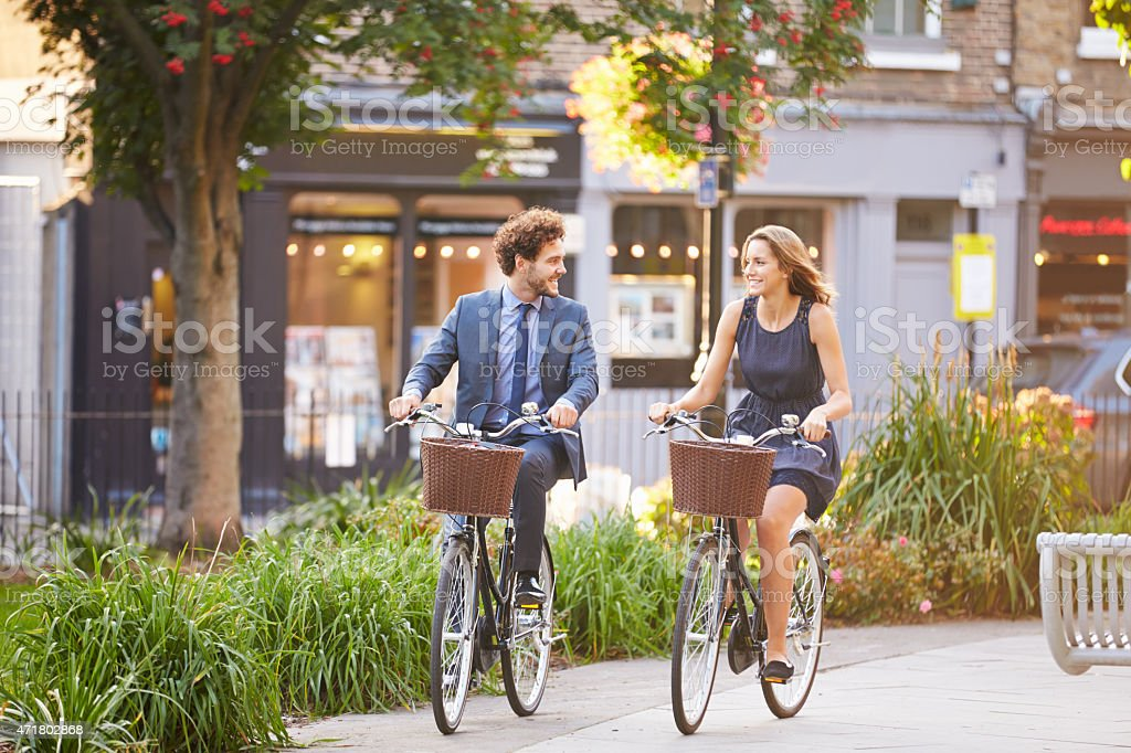 Happy business people riding bikes through city park stock photo