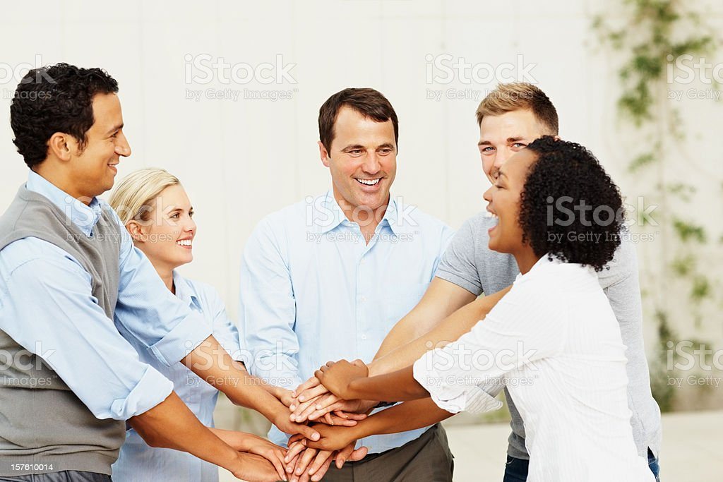 Happy business people standing with their hands together royalty-free stock photo