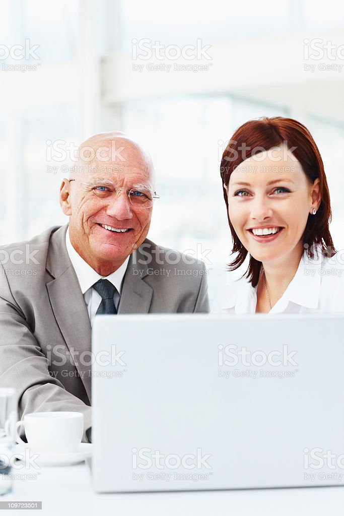 Happy business people working on a laptop at office royalty-free stock photo