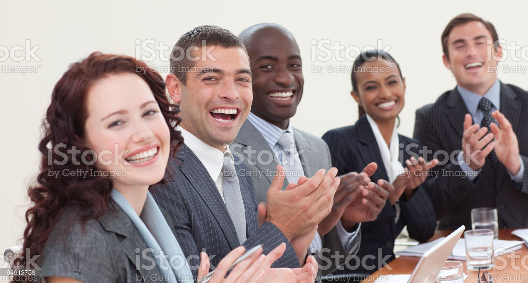 Happy business team laughing and clapping royalty-free stock photo