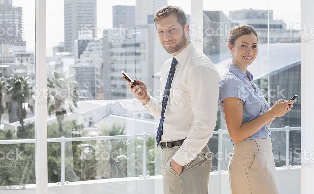 Happy business team standing back-to-back and texting stock photo