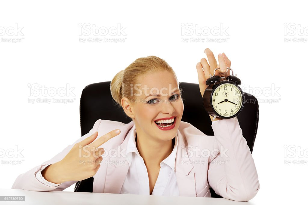 Happy business woman holding alarm clock stock photo